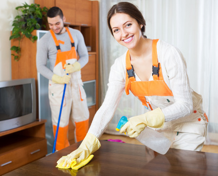 Happy professional cleaners with equipment clean furniture of client house Stock Photo