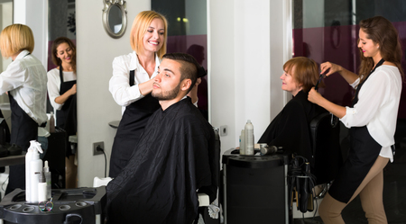 hairtician: Hairdressers making haircuts with scissors for their customers in a hairdressing saloon