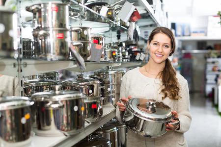 cookware: La mujer joven elige la cacerola en la tienda de utensilios de cocina