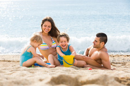 Family vacation parents and children on the sea shore summer day Stock Photo
