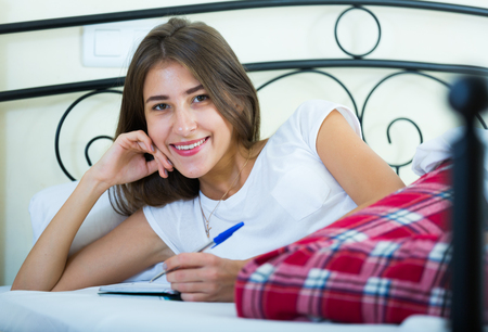 poems: Happy girl lying on bed and writing in diary