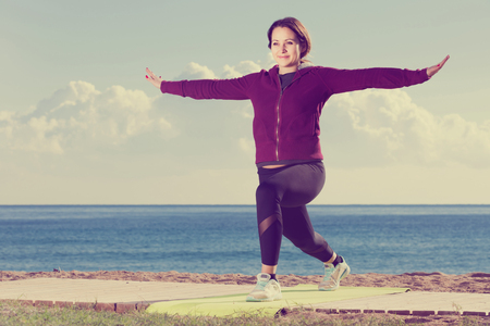young european girl exercising on exercise mat outdoor