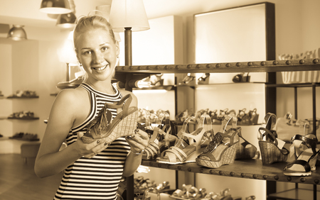 desired: Glad adult woman shopaholic holding desired shoe in fashion boutique