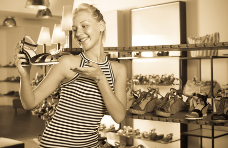 desired: Glad woman shopaholic holding desired shoe in fashion boutique Stock Photo