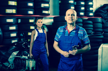Technician man in coveralls standing in car workshop