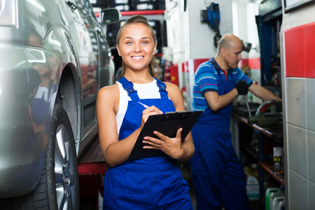 blue overall: positive young woman mechanic in blue overall standing and writing down data in auto workshop