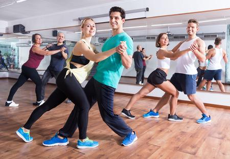 Young men and women dancing a salsa o bachata at a dance hall