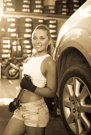 Happy young mechanic woman working on car wheel in service point Stock Photo