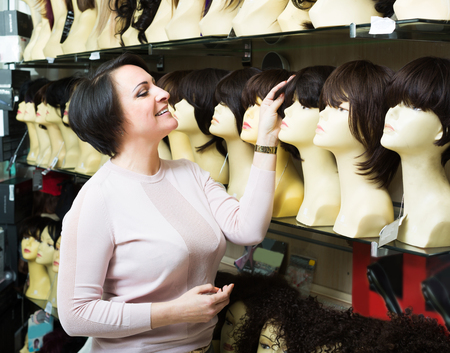 peruke: Happy woman looking at periwigs in shop and smiling