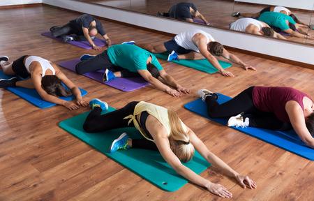 adult learners: adultos felices que clase de yoga en club de deporte