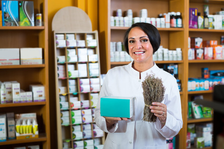 friendly smiling  mature woman in white coat standing with bunch of dried vulnerary herbs in drugstore