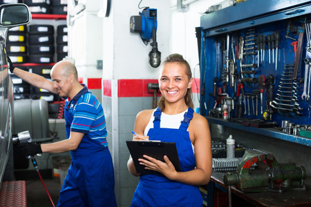 blue overall: cheerful young woman mechanic in blue overall standing and writing down data in auto workshop