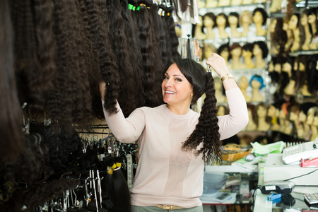 Friendly saleswoman offering wide assortment of natural wigs and hair extensions Stock Photo