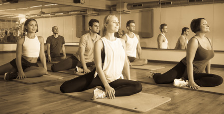 Group of young positive people doing yoga in dance hall. Focus on brunet man