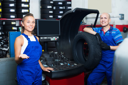 wheel balancing: Two positive technicians working on wheel balancing machinery in car service