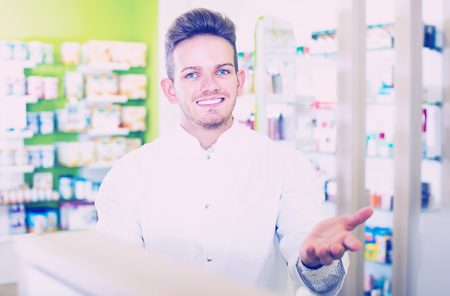 Happy young man pharmacist wearing uniform and working in pharmaceutical shop