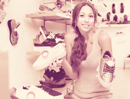 young woman customer choosing one of the two pair of shoes in boutique Stock Photo