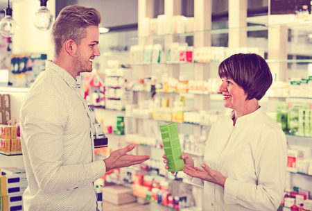 buying questions: Cheerful smiling positive woman pharmacist in white coat helping customers to find item in drug store