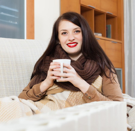 Happy girl with cup near  heater in home