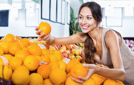 Positive young woman buying oranges on marketplace