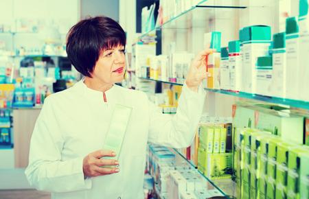diligente: Retrato de mujer contenta farmacéutico positivo diligente en la capa blanca que trabaja en la farmacia