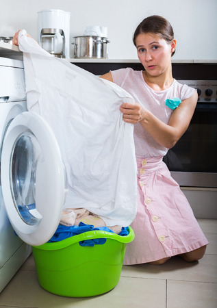 unwashed: Upset adult brunette with musty linen after laundry at home Stock Photo