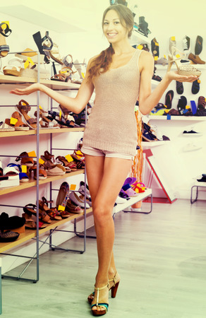 desired: Cheerful female customer showing desired shoe in boutique Stock Photo