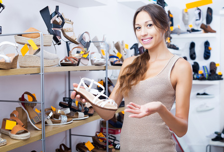 glad young woman holding desired shoe in hands in fashion boutique