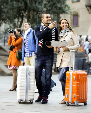 Portrait of attractive tourists with map and baggage in European city. Focus on the right couple Banco de Imagens