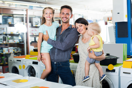 niÑos contentos: Glad family with two children shopping together in shop of household appliances Foto de archivo