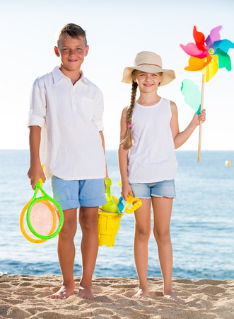 standing together: portrait of boy and girl standing with toys on sandy beach Stock Photo