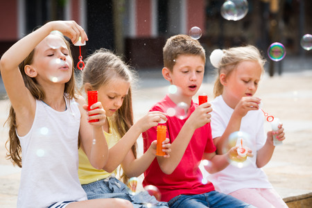 Four cheerful kids in school age sitting together and blowing soap bubbles Stock Photo