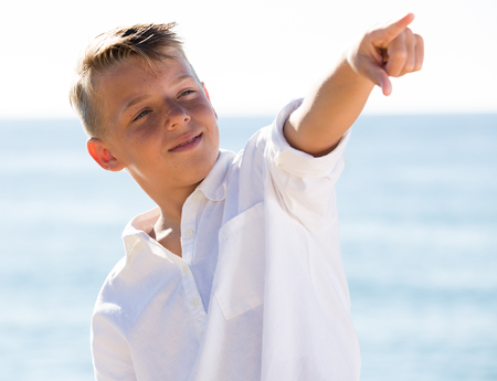cheerful boy in elementary school age standing on beach and pointing aside