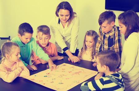 niÑos contentos: Niños contentos de edad elemental sentado en la mesa con juego de mesa y los dados