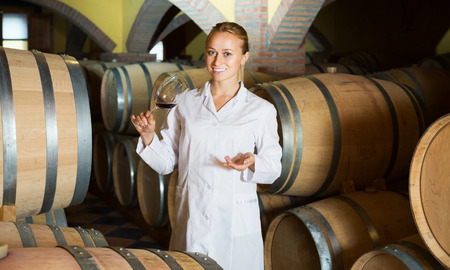 ageing process: Woman in white robe checking ageing process of red wine