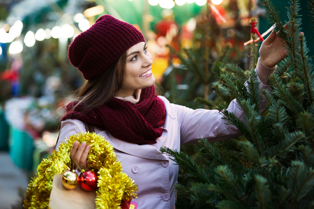 Young woman  choosing New Years tree in fair