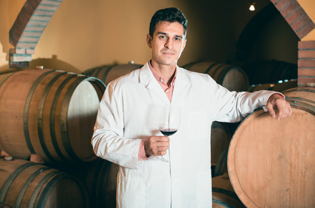 ageing process: serious man in white robe checking ageing process of red wine