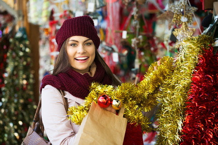 overspending: Portrait of positive girl shopping at festive fair before Xmas