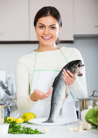 jorobado: Positive girl in white sweater with fresh salmon fish