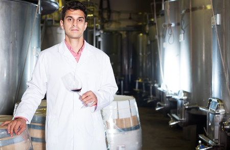 Positive male sommelier checking wine fermentation in winery interior