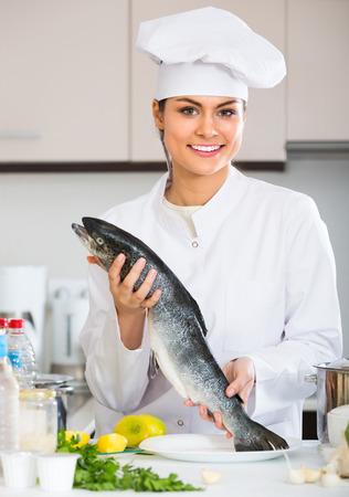 jorobado: trucha arco iris jefe cocinero de sexo femenino joven feliz en la cocina comercial