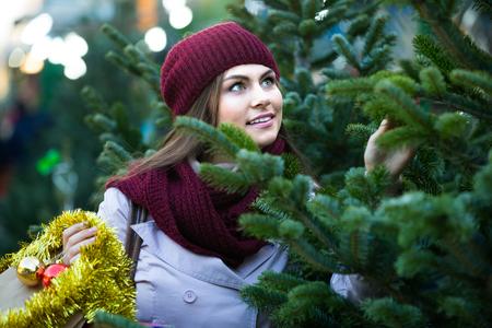 overspending: Happy european woman   buying Christmas tree in market