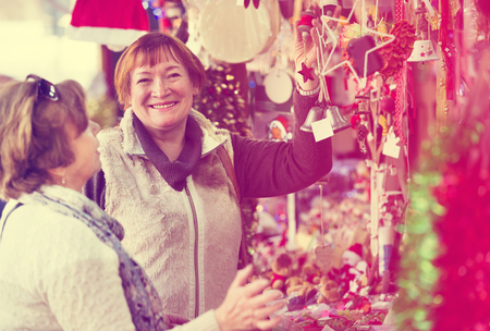 festal: Cheerful female pensioners buying the X-mas decorations and souvenirs at the fair Stock Photo