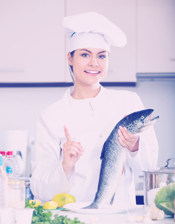 jorobado: Young chef holding carcass of fish in professional kitchen
