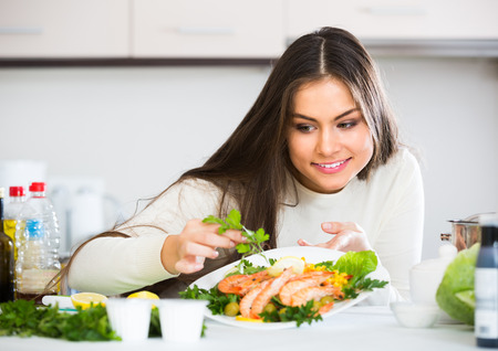 jorobado: Smiling girl in pullover decorating plate with fried prawns at home kitchen Foto de archivo