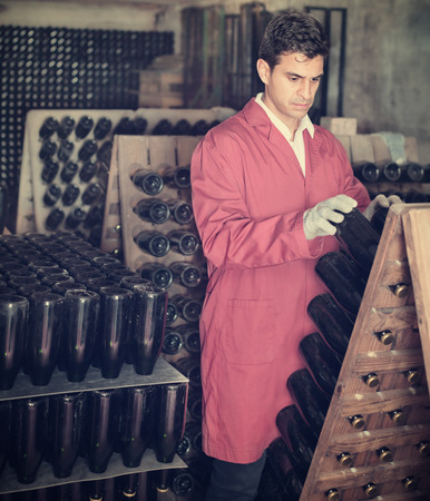 aging american: Portrait of male wine maker in coat taking care of seasoning bottles in a winery cellar Stock Photo