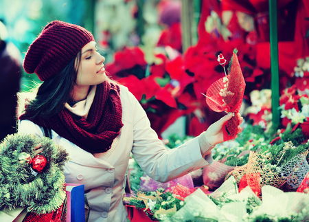 overspending: Young girl staying near counter with the mistletoe at the Xmas fair Stock Photo