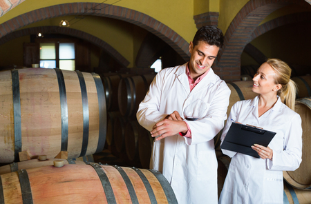 ageing process: Specialists in white robes checking ageing process of wine