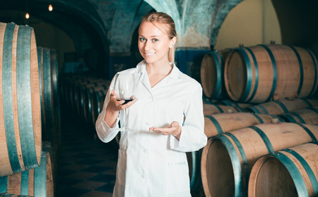 laboratorian: Happy blonde woman in white robe checking ageing process of red wine