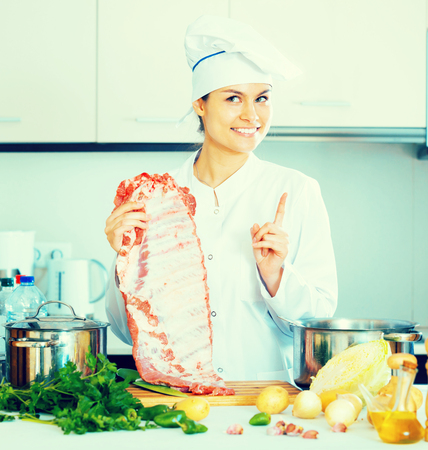 Young female chef working with pork ribs in kitchen